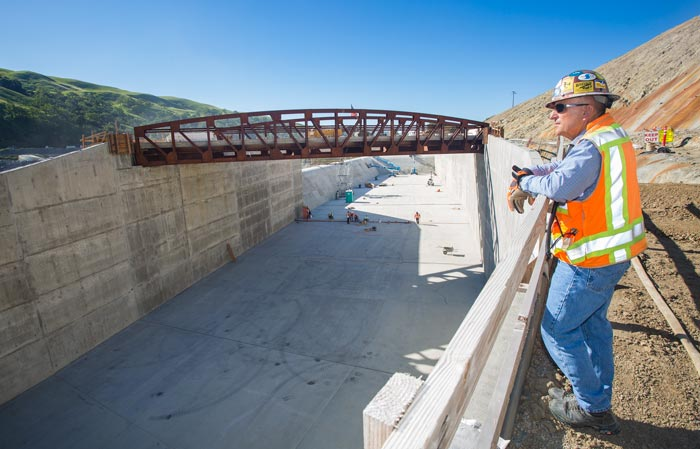 A QA Inspector looks out over the spillway's progress. Crews had to build a bridge across the spillway in order to be able to access it while finishing construction on the rest of the dam.